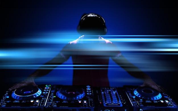 Portret pewnego siebie młodego dj'a ze słuchawkami na głowie miksującego muzykę na mikserze