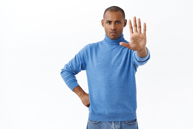 Portret pewnego siebie, poważnie wyglądającego młodego mężczyzny ostrzegającego jako zabezpieczenie, wyciągnij rękę do przodu w stop