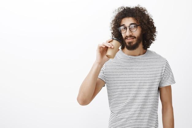 Portret pewnego siebie przystojnego, szczupłego baristy w modnym t-shircie i okularach, pije kawę z kubka i gapi się