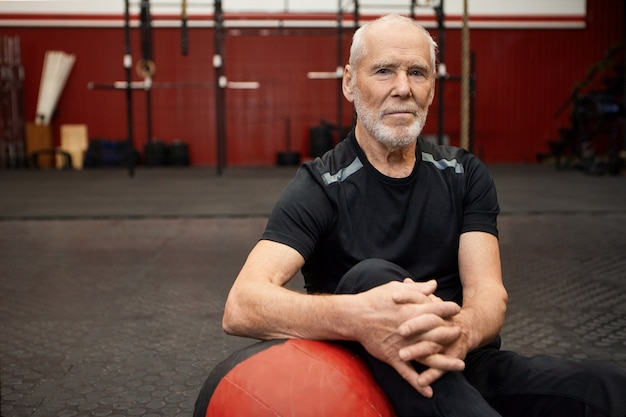 Portret pewnego siebie zdecydowanego kaukaskiego starszego mężczyzny z brodą wybierającego zdrowy, aktywny tryb życia siedzącego na podłodze z piłką, odpoczywającego po intensywnym treningu na siłowni