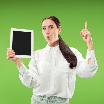 Portret pewnej dorywczo dziewczyny pokazującej pusty ekran laptopa na białym tle nad zieloną ścianą