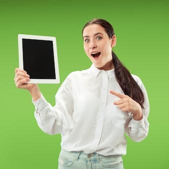 Portret pewnej dziewczyny dorywczo pokazuje pusty ekran laptopa na białym tle nad zieloną ścianą.