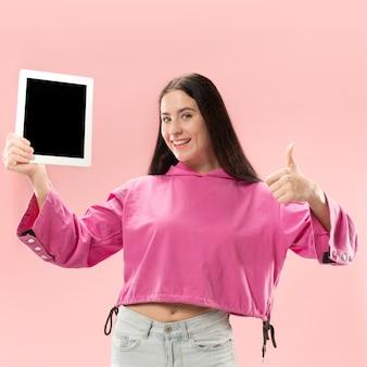 Portret pewnej dziewczyny dorywczo pokazuje pusty ekran tabletu na białym tle nad różowym tłem.
