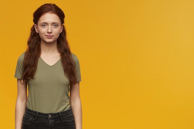 Portret pewnej siebie atrakcyjnej młodej kobiety z długimi rudymi włosami stojącej na białym tle nad żółtą ścianą