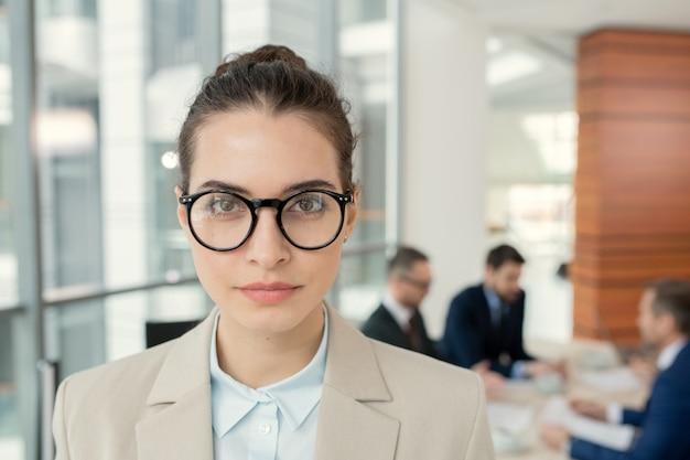 Portret pewnej siebie, atrakcyjnej prawniczki w okrągłych okularach, stojącej przeciwko kolegom omawiającym dokumenty w tle