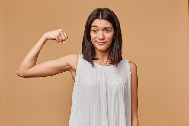 Portret pewnej siebie dziewczyny, dumnej ze swojej siły, zaciska pięść i pochyla rękę, by pokazać odizolowane mięśnie