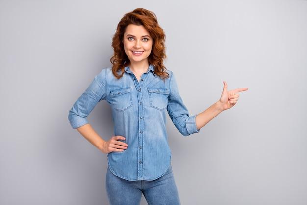 Portret pewnej siebie, fajnej kobiety promotor wskazujący palec wskazujący copyspace zasugeruj wybierz reklamy promo porady porady noś dobrze wyglądające ubrania odizolowane na szarej ścianie
