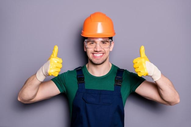 Portret pewnej siebie fajnej osoby zajmującej się naprawami ma pomarańczowy kask żółte rękawiczki pokaż kciuk w górę znak zatwierdź zrekonstruowane mieszkanie pokój nosić zieloną koszulkę pomarańczowy odizolowany szary kolor ściana