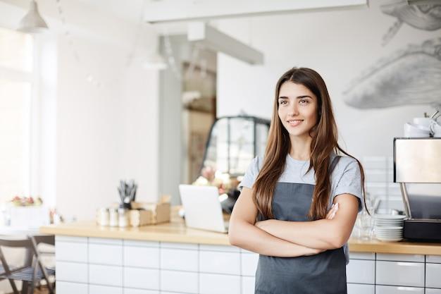 Portret pewnej siebie i młodej kobiety posiadającej i prowadzącej odnoszącą sukcesy firmę w kawiarni i cukierni.