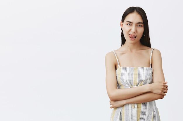 Portret pewnej siebie i zmysłowej dorosłej kobiety w stylowym stroju, pokazującej język, trzymającej ręce na piersi i wpatrującej się z odważnym i pewnym siebie wyrazem, pragnienie czegoś na szarą ścianę
