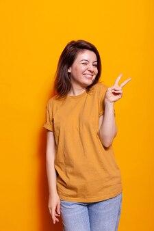 Portret pewnej siebie kobiety pokazujący znak pokoju palcami
