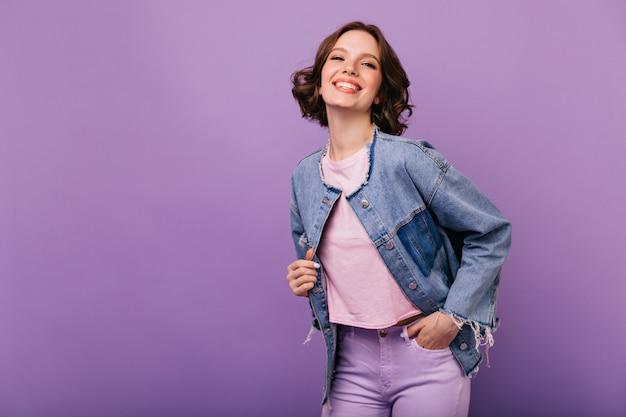 Portret pewnej siebie młodej kobiety w modnej kurtce oversize. elegancka uśmiechnięta dziewczyna pozuje z przyjemnością.