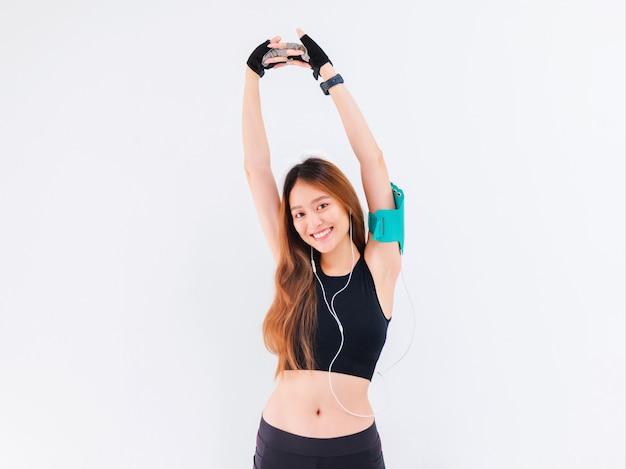 Portret pewnej siebie pięknej azjatyckiej fitness kobiety słuchania muzyki i rozgrzewki przed ćwiczeniami na białym tle.