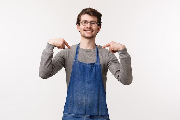 Portret pewnej siebie przystojnej profesjonalnej męskiej baristy w fartuchu, chwalący się właściciel kawiarni, przygotowuje najlepszą kawę w mieście, pokazując się chełpliwie, uśmiechając się jak profesjonalista, biała ściana