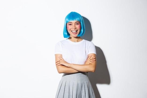 Portret pewnej siebie stylowej azjatki w niebieskiej krótkiej peruce, przebranej na imprezę pop lub halloween, skrzyżowane ramiona na piersi i uśmiechnięta szczęśliwa, stojąca.