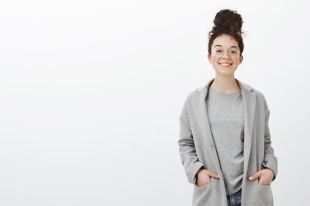 Portret pewnej siebie, szczęśliwej, przystojnej dziewczyny z kręconymi włosami uczesanymi w kok, noszącej szary płaszcz i okulary, trzymającej się za ręce w kieszeniach i uśmiechającej się wesoło