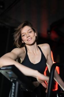 Portret pewnej zdrowej brunetki ubranej w strój sportowy stojący na siłowni