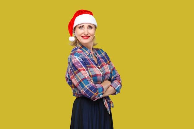 Portret pewnie atrakcyjna dorosła kobieta w czerwonej czapce santa i kraciastej koszuli stojącej i zamkniętej dłoni z uśmiechniętymi zębami, patrząc na kamery. wewnątrz, strzał studyjny, żółte tło