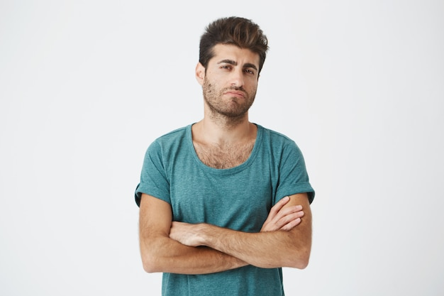 Portret pewnie atrakcyjnego młodego hiszpańskiego faceta w niebieskiej koszulce i stylowej fryzurze, krzyżujący ręce, będący bardzo zazdrosnym widząc byłą dziewczynę z nowym mężczyzną.
