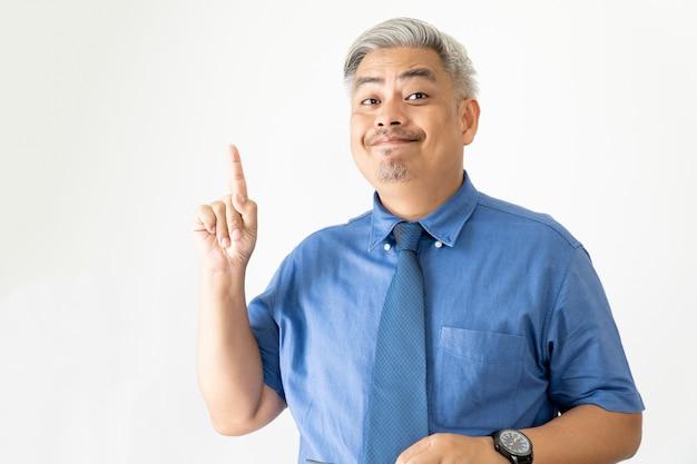 Portret pewnie azjatycki biznes człowiek w okularach i koszulę z krótkim rękawem, wskazując