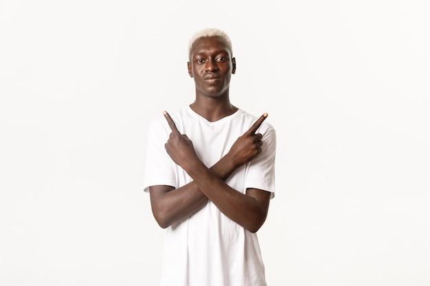 Portret pewnie blond afroamerykanin, wskazując palcami w bok, pokazując warianty wyborów