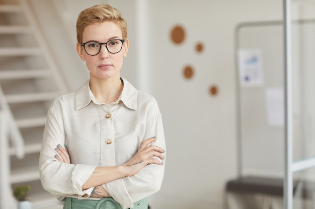 Portret pewnie businesswoman stojąc z rękami skrzyżowanymi w biurze, kopia przestrzeń