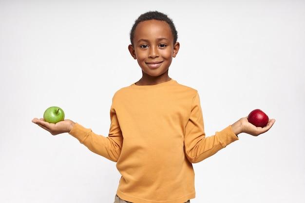Portret pewnie czarnego chłopca z wesołym uśmiechem pozowanie na białym tle z zielonymi i czerwonymi jabłkami w jego rękach