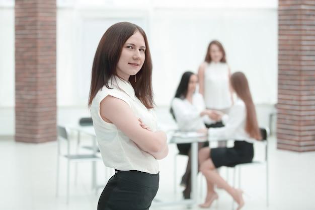 Portret pewnie młody biznes kobieta na tle pakietu office.