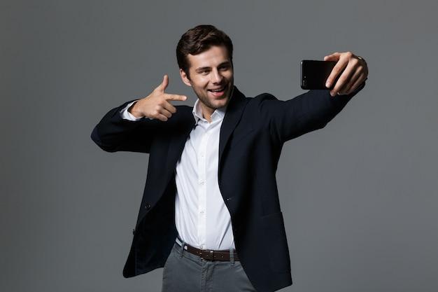 Portret pewnie młody biznesmen ubrany w garnitur na białym tle nad szarą ścianą, biorąc selfie, wskazując palcem
