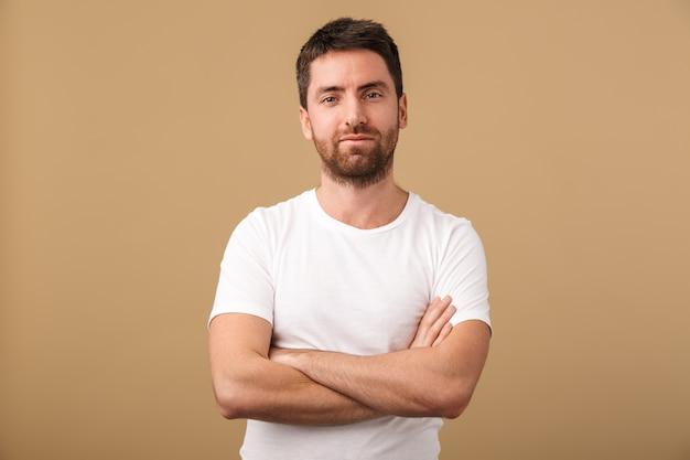 Portret pewnie młody mężczyzna ubrany niedbale stojący na białym tle nad beżem