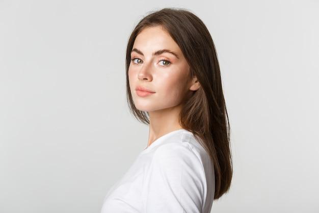 Portret pewnie piękna brunetka kobieta odwracając twarz w aparacie z marzycielskim spojrzeniem, biały.
