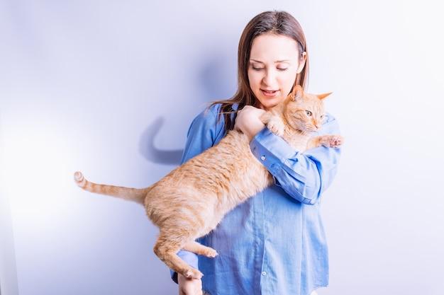 Portret pewnie piękna młoda kobieta przytulanie jej pomarańczowy kot w białym tle. koncepcja opieki nad zwierzętami. miłość do zwierząt. animalistyczny