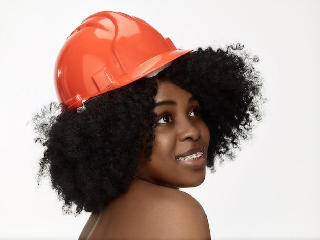 Portret pewnie pracownica w pomarańczowym kasku