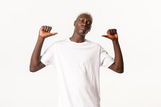 Portret pewnie przystojny afroamerykanin blondyn, wskazując palcami na siebie bezczelny i dumny, stojąc na białym tle