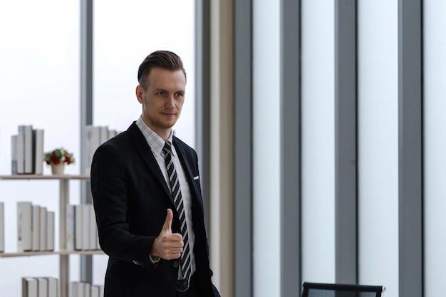 Portret pewnie przystojny biznesmen kaukaski w formalnym garniturze stojący i kciuk w nowoczesnym biurze, szczęśliwa praca. udany pomysł na biznes.