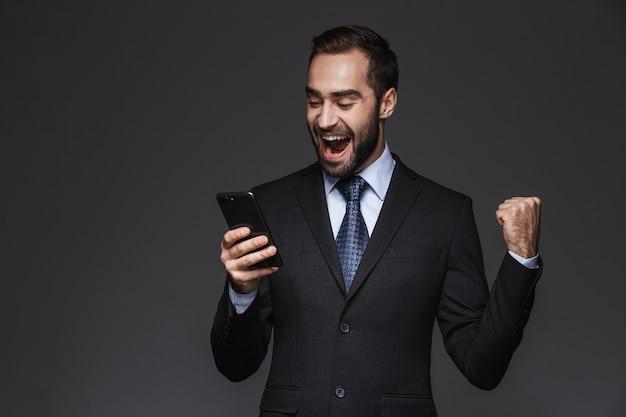 Portret pewnie przystojny biznesmen na sobie garnitur na białym tle, przy użyciu telefonu komórkowego, świętuje sukces