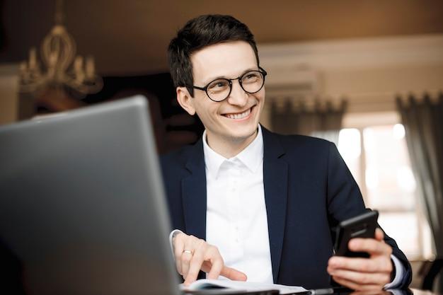 Portret pewnie przystojny biznesmen pracuje trzymając smartfon i wskazując palcem w swoim notesie patrząc od śmiechu ubrany w garnitur.