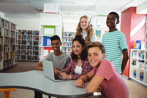 Portret pewnie studentów siedzi przy biurku