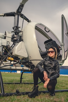 Portret pewnie stylowej blondynki animowanej dziewczyny siedzącej w pobliżu otwartego helikoptera na zielonym polu latania w aeroklubie w wiosenny dzień