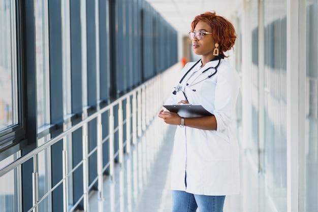 Portret pewność african american kobiet lekarz medycyny pisania notatek pacjenta na białym tle na tle okien korytarza kliniki szpitalnej. pozytywny wyraz twarzy