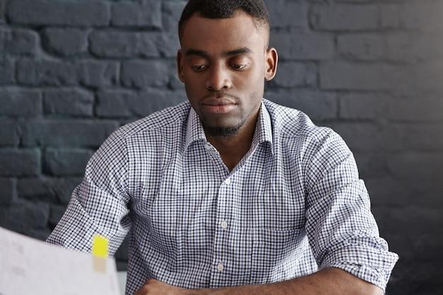 Portret pewność atrakcyjnego afro-amerykańskiego pracownika biurowego analizowania dokumentów podczas obiadu w restauracji