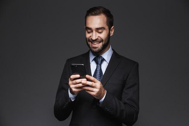 Portret pewność biznesmen przystojny na sobie garnitur na białym tle, przy użyciu telefonu komórkowego