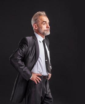 Portret pewność biznesmena w garniturze na czarnej ścianie