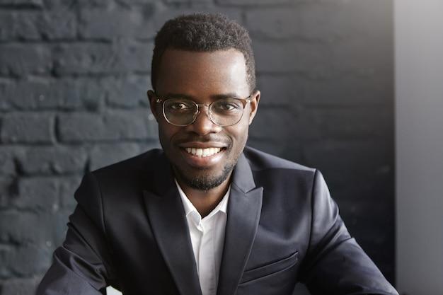 Portret pewność i sukcesy młody biznesmen african-american na sobie stylowe okulary
