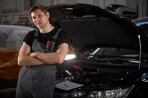 Portret pewność mechanika kaukaski w mundurze, pozowanie na kamery w serwisie samochodowym