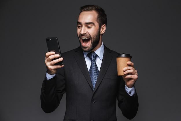 Portret pewność przystojny biznesmen ubrany w garnitur na białym tle, trzymając kubek na wynos, przy użyciu telefonu komórkowego