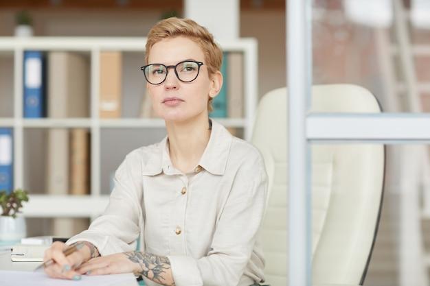 Portret pewność tattoed businesswoman siedząc przy biurku w biurze, kopia przestrzeń
