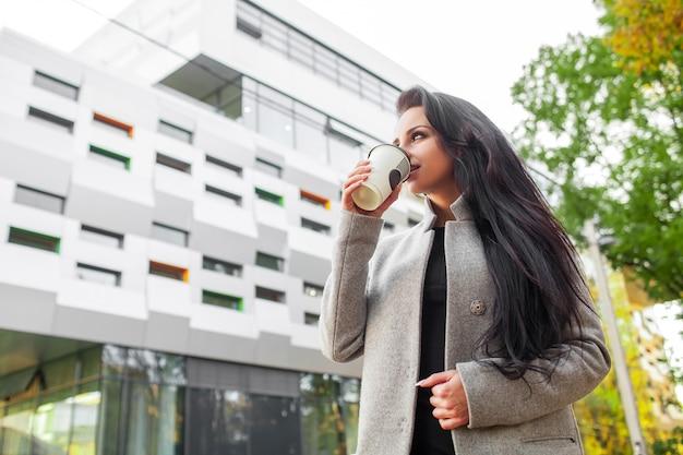 Portret pewności siebie biznesowa kobieta z kawą iść obok biura.