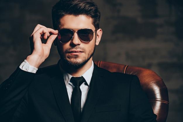 Portret pewności siebie. portret młodego przystojnego mężczyzny w garniturze, dostosowując okulary przeciwsłoneczne i patrząc na kamerę, siedząc w skórzanym fotelu na ciemnoszarym tle