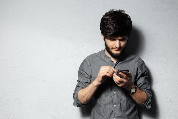 Portret pewny siebie młody chłopak za pomocą smartfona.